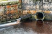 image of h20  - An overflow pipe at a water treatment works spewing water in to a stream - JPG