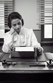 pic of 1950s style  - Young bored secretary working at office desk with typewriter 1950s style - JPG