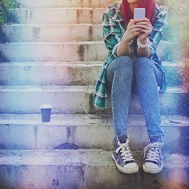 pic of takeaway  - Hipster millennial teenage girl with smart phone and takeaway coffee sitting on stairs in park - JPG