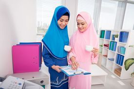 picture of muslim  - Muslim business women drinking coffee and discussing document - JPG