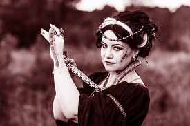 stock photo of ugly  - Ugly woman with snake - JPG