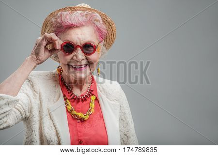 poster of Happy souls never age. Waist up portrait of Smiling fashionable old woman in red sunglasses wearing fashion clothes while posing for photographer. isolated on gray background. Copy space