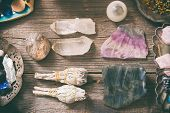 Natural gemstones, white sage and incense on wooden board poster