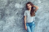 Young beautiful model wearing blank gray t-shirt and jeans posing against rough concrete wall, minim poster