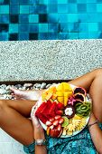 Girl relaxing and eating fruit plate by the hotel pool. Exotic summer diet. Photo of legs with healt poster