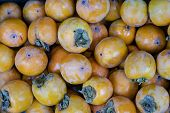 Ripe Persimmons Tiled On A Market Stall. Organic Persimmon Fruits In Pile At Local Farmers Market In poster