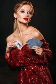 Attractive Girl In Red Shiny Dress Hiding Joker Card In Dress Isolated On Black, Looking At Camera poster