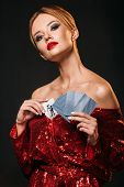 Attractive Girl In Red Shiny Dress Hiding Joker Card In Dress Isolated On Black poster