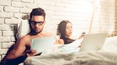 Young Business Couple Working In Bed At Night Time. Businessman Working On Computer In Bed While Wif poster