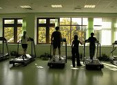 stock photo of sweatshop  - people with teacher in health club and autumn in window - JPG