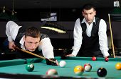 stock photo of snooker  - young professional people play snooker in the billiard club dark - JPG