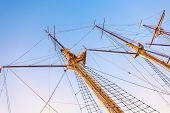 Sailboat masts in sunset light on sky background