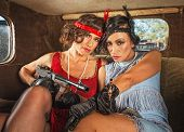 image of tommy-gun  - Pair of pretty 1920s female gangsters in car - JPG