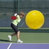 stock photo of pickleball  - Digital image of senior female pickleball player hitting backhand shot directly at the camera - JPG
