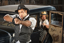 pic of tommy-gun  - Tough 1920s vintage gangsters outside aiming guns from car - JPG