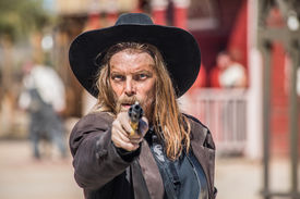 pic of foursome  - Cowboy Points Gun at You in Town - JPG