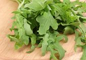 pic of rocket salad  - Fresh rucola salad or rocket lettuce leaves on wooden board isolated on white  - JPG
