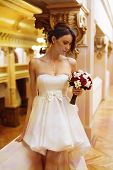 stock photo of clevage  - Beautiful young bride with a short gown and a bouquet in ger hand looking down - JPG