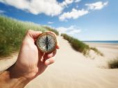 stock photo of deserted island  - Hand holding a compass on the beach by sea concept for guidance - JPG
