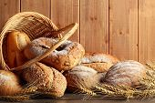 stock photo of whole-grain  - Whole grain wheat bread in basket with wheat ears - JPG