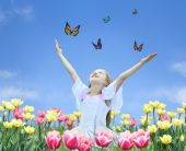 foto of young girls  - little girl in tulips with hands up and butterfly collage - JPG