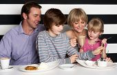 pic of eatables  - Cheerful family of four enjoying breakfast at a restaurant - JPG