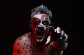 picture of madman  - The scary zombie is lying in the studio and stretching - JPG