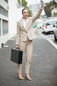 picture of hail  - Young businesswoman hailing a cab outside in the city - JPG
