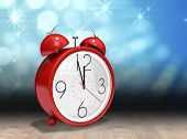 stock photo of count down  - Alarm clock counting down to twelve against shimmering light design over boards - JPG