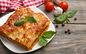 image of lasagna  - Portion of tasty lasagna on wooden table - JPG