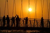 picture of gang  - People silhouettes on the sunset on Lakshman Jhula bridge over Ganges in Rishikesh - JPG