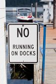 foto of dock a lake  - A sign posted stating no running on docks with a background of boats and a lake - JPG