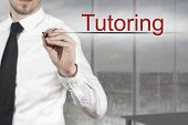 stock photo of tutor  - businessman in office writing tutoring in the air - JPG