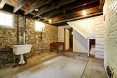 picture of stone house  - Basement empty room interior with stone wall trim and brick wall with fireplace - JPG