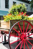 stock photo of wagon wheel  - An old wood cart with large red wagon wheel used as a garden planter - JPG