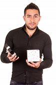 foto of disappointed  - charming young man holding a gift box looking disappointed isolated on white - JPG