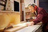 stock photo of sawing  - Female Apprentice Using Circular Saw In Carpentry Workshop - JPG