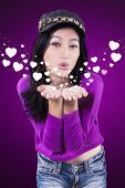 picture of blowing  - Lovely young asian teenage girl with casual clothes blowing kiss at the camera against purple background - JPG