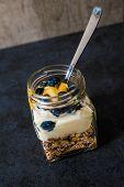image of muse  - A jar of healthy swiss museli yogurg blackberries and honey on a black slate background - JPG