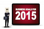picture of anonymous  - Anonymous businessman with a cardboard head standing next to the board of business goals for 2015 isolated over white - JPG