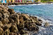 stock photo of curacao  - Colorful buildings beyond a rocky seawall in Curacao - JPG