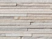 stock photo of wall-stone  - beautiful wall of natural light gray and beige narrow stones for finishing of external facades and interiors