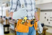 image of pliers  - Technician with tool belt around waist holding pliers against workshop - JPG