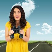 picture of binoculars  - Smiling casual young woman holding binoculars against road leading out to the horizon - JPG