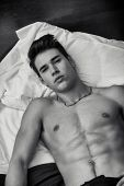 image of laying-in-bed  - Handsome shirtless athletic young man laying in bed at night looking at camera - JPG