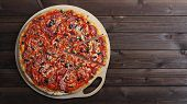 image of hot fresh pizza  - freshly baked hot pizza on a wooden table - JPG