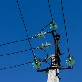 foto of insulator  - concrete support with elecyrical insulators and wires against the blue sky - JPG