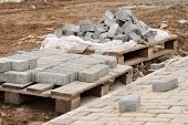 stock photo of paving  - Elements of paving slabs paving stones stacked on a pallet stacked and rolled around a bunch lined sidewalk
