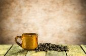 stock photo of patron  - Coffee cup and coffee beans on wooden table and blurred background - JPG