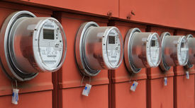 stock photo of power lines  - Line up of five electric power meters on red electrical panels - JPG